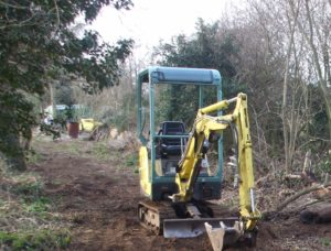 An unusually idle digger, half way through removing an enormous stump and its associated abandoned rabbit earth piles