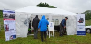 Volunteers sorting out the new shop tent - in heavy rain!